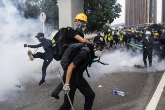 Demonstrators stand in a cloud of tear gas during a protest in Yuen Long.