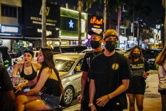 上个月底,行人经过在吉隆坡孟沙区一家酒吧坐在户外的顾客。