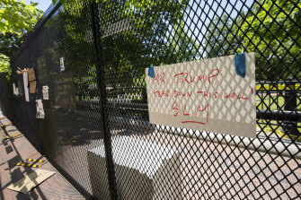 Signs left by demonstrators are taped to the perimeter fencing outside the White House in Washington on Sunday.