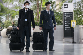 Air China flight attendants wearing disposable face masks walk through the departure hall at San Francisco International Airport in San Francisco as the US funnels flights through a selection of airports.
