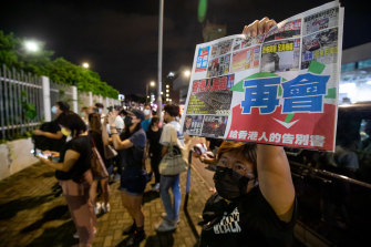 A supporter holds the latest newspaper outside the headquarters of the Apple Daily on Thursday.
