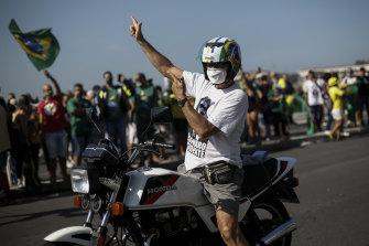 A supporter of the Brazilian President Jair Bolsonaro making a gun sign takes part in a rally in Rio de Janeiro.