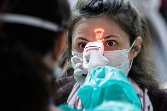 A health worker screens the temperature of an airline passenger arriving from Italy at Debrecen International Airport in Hungary.