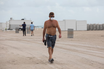 A man wears a protective mask while walking along the beach in Miami Beach, Florida.