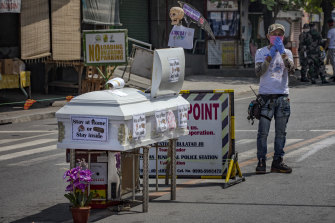 A coffin is part of a street display warning residents of Santo Tomas, Philippines, to stay home during the coronavirus outbreak.