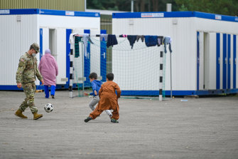 A US soldier plays football with recently arrived Afghan refugees in Germany last month.
