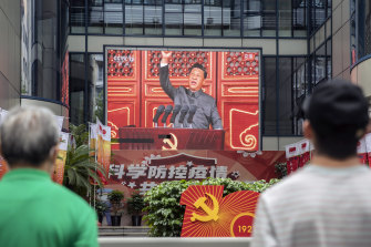 Pedestrians watch a screen showing a live news broadcast of Chinese President Xi Jinping speaking at a ceremony marking the centenary of the Chinese Community Party.