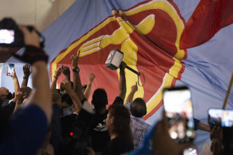 Supporters of the opposition Workers' Party rejoice against the backdrop of a party banner as results are announced.
