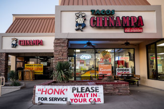 A sign instructs customers to wait in their cars outside a restaurant in El Paso, Texas' worst spot for COVID infections.