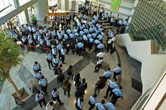 Police officers gather at the lobby of headquarters of Apple Daily in Hong Kong on Thursday.