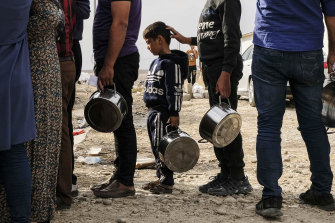 Syrian refugees fleeing the Turkish incursion in Northern Syria wait to receive water, bread and lentil soup as more than 200 arrive at the Bardarash IDP camp on October 17.