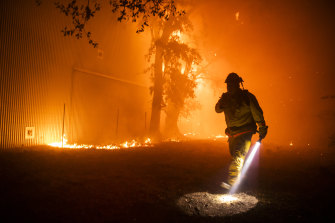 A firefighter uses a flashlight to search the perimeter of a building at the Soda Rock Vineyards during the Kincade fire in Healdsburg.