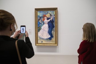 Viewers take in Renoir's famous Dance at Bougival painting at the NGV.