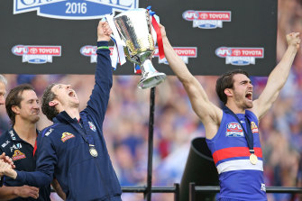 Western Bulldogs great Bob Murphy holds up the 2016 premiership cup with Easton Wood.