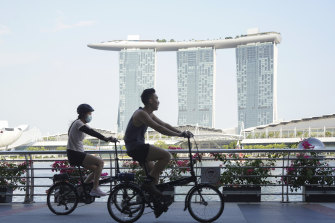 Cyclists ride past the Marina Bay Sands Hotel in Singapore, where curbs have been tightened this week.