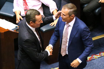 Premier Mark McGowan and Health Minister Roger Cook celebrate on the floor of WA's Legislative Assembly after the passage of the government's euthanasia legislation in 2019.