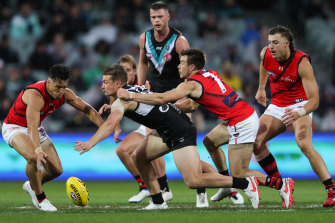 Port Adelaide's Ollie Wines takes on  Dylan Shiel and Zach Merrett during the win over the Bombers on Saturday.