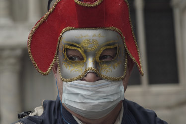 A Russian tourist dons a carnival mask and protective mask for Carnival. The event was cancelled two days before it was due to finish.