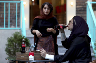 An Iranian drinks a Coca-Cola and smokes a Marlboro cigarette at a cafe in downtown Tehran.