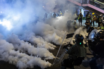 Riot police walk toward a cloud of tear gas as they attempt to disperse demonstrators during a protest in the Sheung Wan district of Hong Kong.