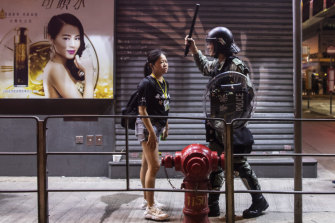 A riot police stands off against a woman during a protest in the Mong Kok district of Hong Kong, China, on Saturday night.
