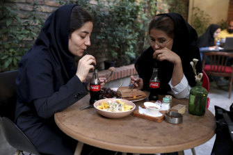 Two Iranians drink Coca-Cola at a cafe in downtown Tehran.