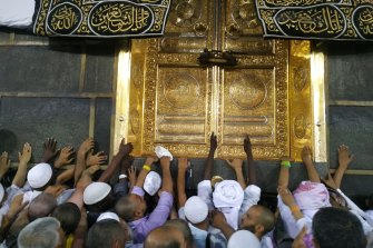 Pilgrims touch the Kaaba, which they believe to be the first mosque.