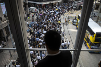 A man watches the growing protest on Friday from a pedestrian footbridge in Hong Kong's Central district.