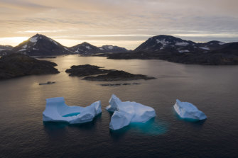 Icebergs float away as the sun rises near Kulusuk, Greenland. Scientists are trying to understand the alarmingly rapid melting of the ice.