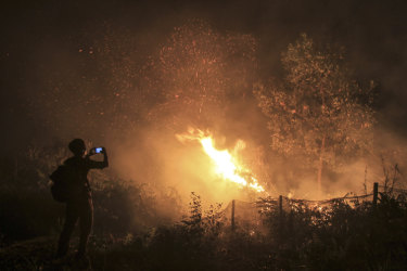 A man uses his mobile phone to take photos of a forest fire in Kampar, Riau province, Indonesia.
