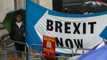 """Demonstrators hold a """"Brexit Now"""" banner outside the Supreme Court in London."""