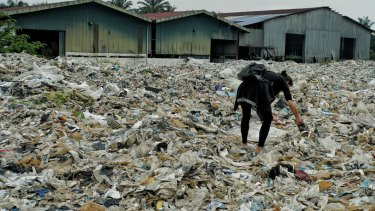 A member of the Kuala Langat environment NGO picks up  plastic waste at a shuttered illegal plastic recycling factory in Jenjarom.