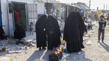 Women buy food at Al Hawl camp, Syria.