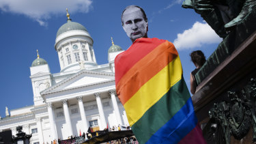 A man with a Putin mask and a rainbow flag attends a rally against the policy of US President Donald Trump and Russian President Vladimir Putin in central Helsinki on Sunday.