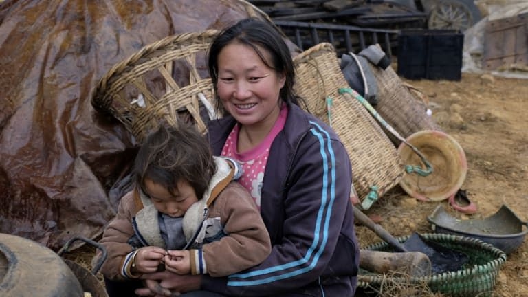 Xu Xuanhua, 31, the mother of three children embraces her 3-year old son Xia Zhongshuia in Xuanqiao Village, Zhaotong City of Yunnan Province in November