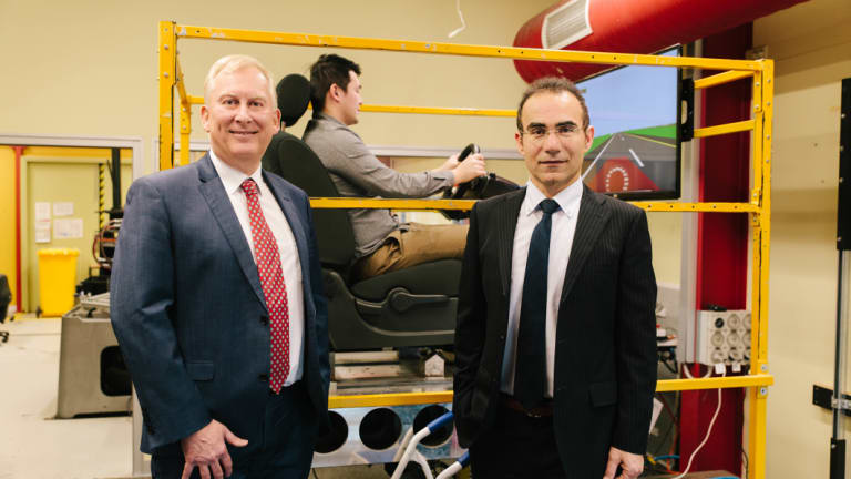 Professor Stephen Robinson and Associate Professor Mohammad Fard stand in front of the simulator.