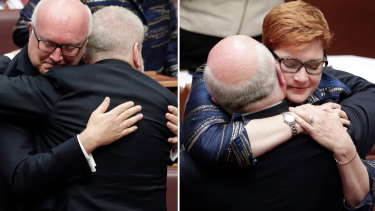 Senator Brandis is congratulated by Mitch Fifield and Marise Payne.