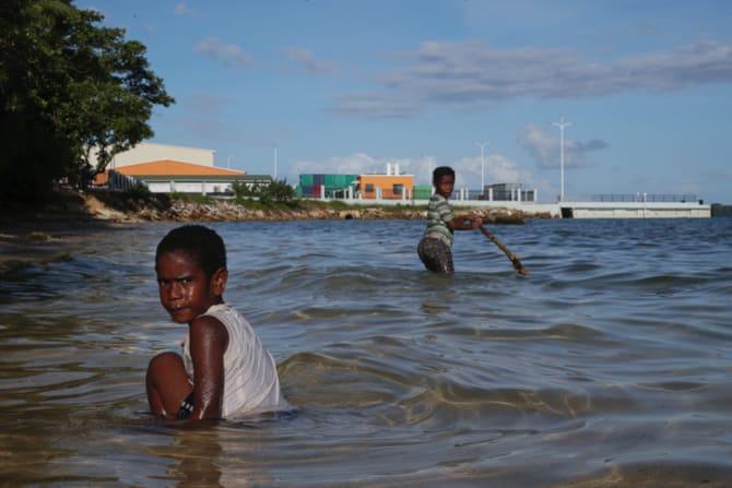 Children play near a new wharf in Luganville, Vanuatu.