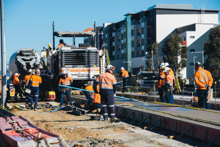 Construction workers laying the light rail concrete slab on Flemington road.