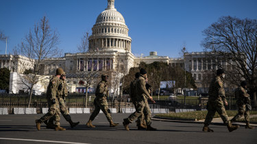 Members of the National Guard walk past a security perimeter outside the US Capitol as preparations are made ahead of the presidential inauguration in Washington.