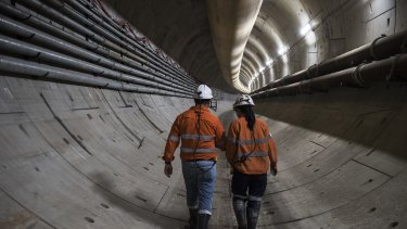 Workers walk down a section of the metro beneath Sydney Harbour.