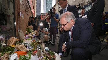 Scott Morrison places flowers outside Pellegrini's on Tuesday morning.