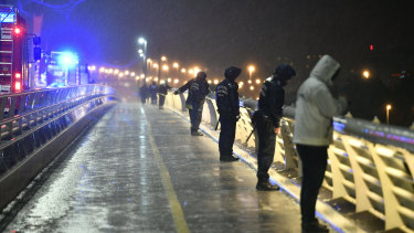 Rescuers and police officers inspect the River Danube from a landing dock after a tourist boat crashed with another ship.