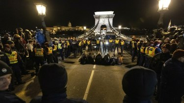 Police confront the crowd on the Chain Bridge during a protest against  labour laws in Budapest, Hungary, on Saturday.