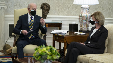 Senator Tammy Baldwin listens as President Joe Biden holds up a microchip during a meeting with lawmakers to discuss US supply chains.