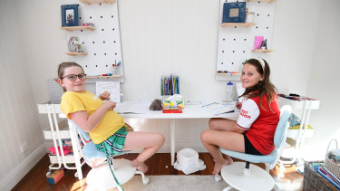Eight-year-old Grace Merriman (left) and her nine-year-old sister Audrey learn from their Brisbane home.