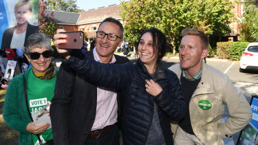 Greens leader Richard Di Natale (centre) smiles for a selfie with their hope for Higgins, Jason Ball (right).