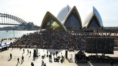 Mourners sitting on the Opera House steps for Bob Hawke's memorial.