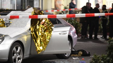 A car that was damaged in the shooting is covered in thermo foil and surrounded by debris at the scene in Hanau, Germany.