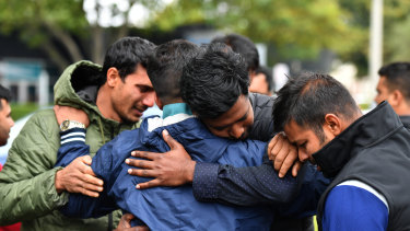 Friends of a man missing  after the mosque shooting grieve outside a refuge centre in Christchurch.